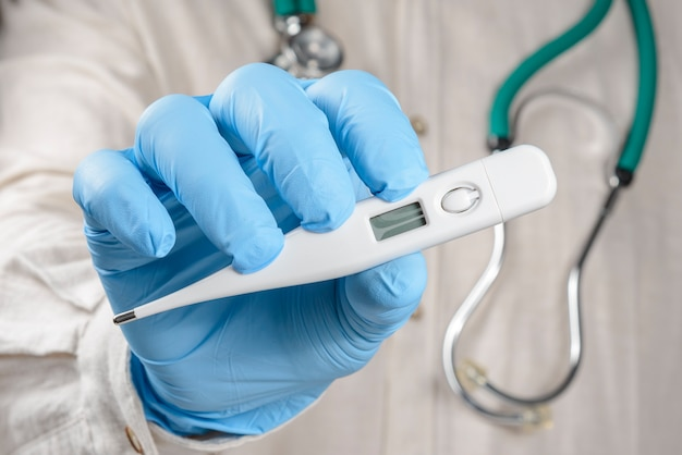 Healthcare professional holding thermometer wearing protective gloves