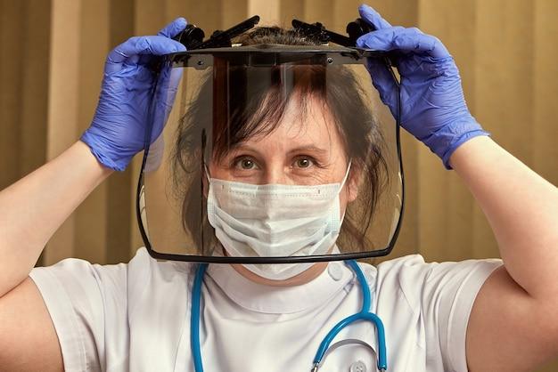 Медицинский работник в медицинской защитной маске, перчатках и очках надевает хирургическое оборудование, чтобы защитить себя во время пандемии коронавируса.