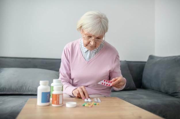 Здравоохранение. старшая женщина с плохим зрением, исследующая лекарства