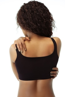 Healthcare, spine pain, posture. slim tanned woman's back on white studio background. african-american model with well-kept shape and skin. beauty, self-care, weight loss, fitness, slimming concept.