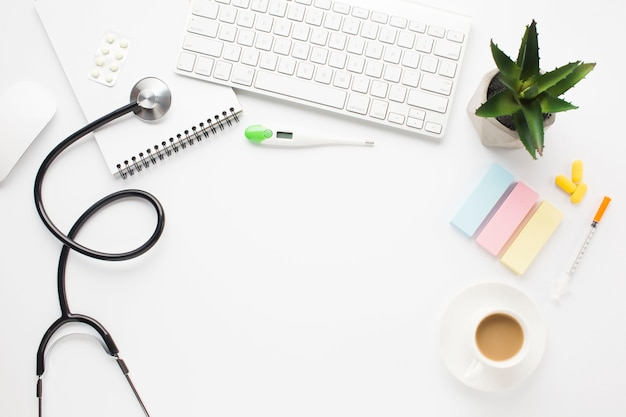 Healthcare tools; medicine; coffee; and succulent plant on white surface