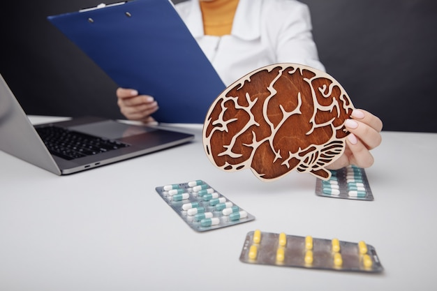 Healthcare and treatment concept doctor holding wooden brain