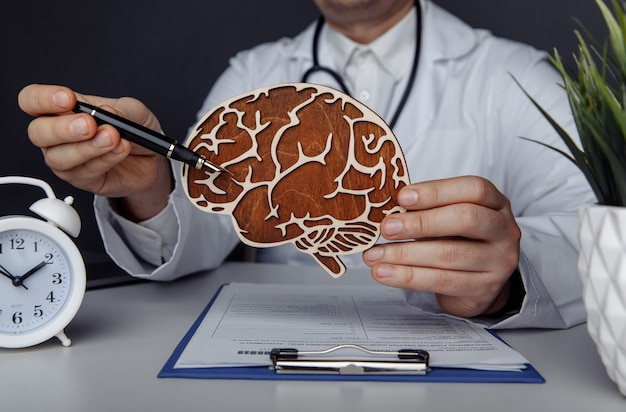 Healthcare, treatment and patalogy concept. male doctor showing wooden brain.