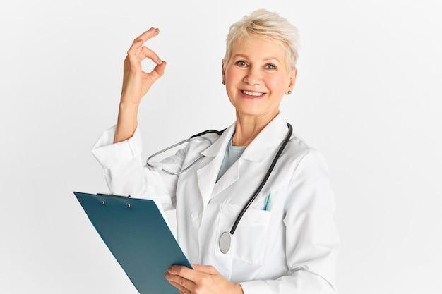 Здравоохранение, лечение, болезни и исцеление. современная успешная зрелая женщина-врач в медицинском комбинезоне, держащая буфер обмена и делающая хорошо жест