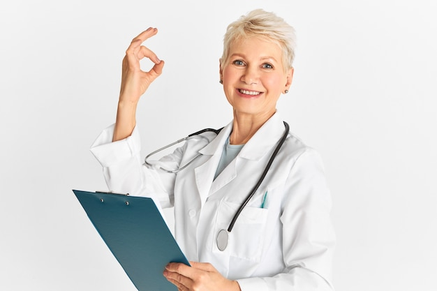 Healthcare, treatment, sickness and healing. modern successful mature female doctor in medical overalls holding clipboard and making ok gesture