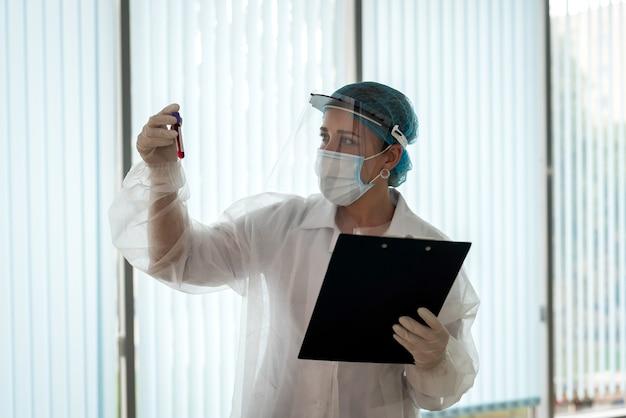의료 노동자는 환자 결과와 클립 보드를 잡고 테스트 튜브를 봐
