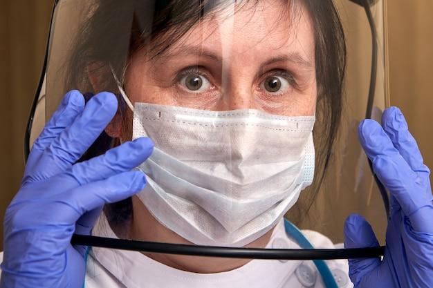 의료 종사자는 투명한 안면 보호대와 수술용 마스크를 착용합니다.