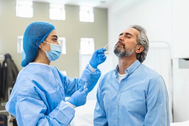 Медицинский работник с защитным снаряжением делает мазок на коронавирус пожилому мужчине. мазок из носа на covid19.