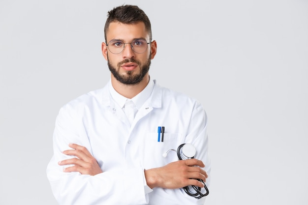 의료 종사자, 코로나바이러스, covid-19 전염병 및 보험 개념. 흰 코트, 안경을 쓴 진지한 젊은 의사의 클로즈업, 환자의 말을 잘 듣고, 팔짱을 끼고, 청진기를 들고 있습니다.