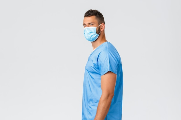 의료 종사자, covid-19, 코로나바이러스 및 예방 바이러스 개념. 자신감 넘치는 잘 생긴 의사, 수술복을 입은 남자 간호사, 의료 마스크 서 있는 프로필, 확고한 표정으로 카메라를 돌리는