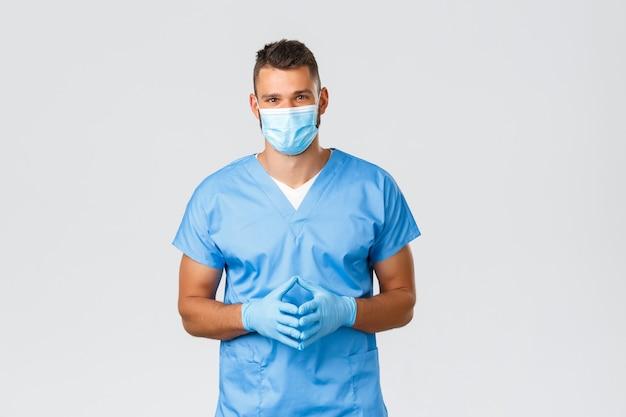 医療従事者、covid-19、コロナウイルスおよび予防ウイルスの概念。フレンドリーなハンサムな医者、スクラブと医療マスクの看護師、カジュアルなスクリーニング中に患者の話を聞く、灰色の背景