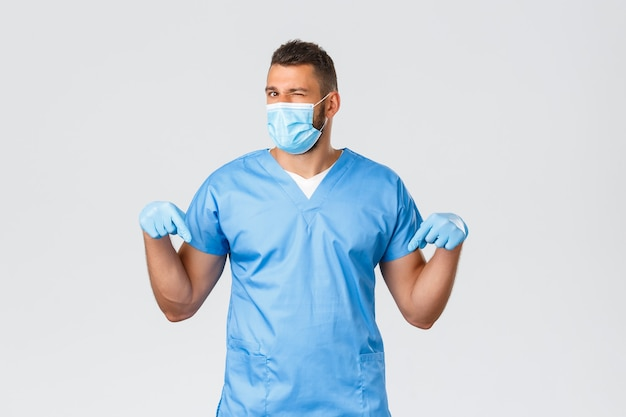 医療従事者、covid-19、コロナウイルスおよび予防ウイルスの概念。ハンサムな生意気な医者は彼らの研究室の診療所で試写会をするように誘い、スクラブの看護師はウィンクカメラを下に向けます