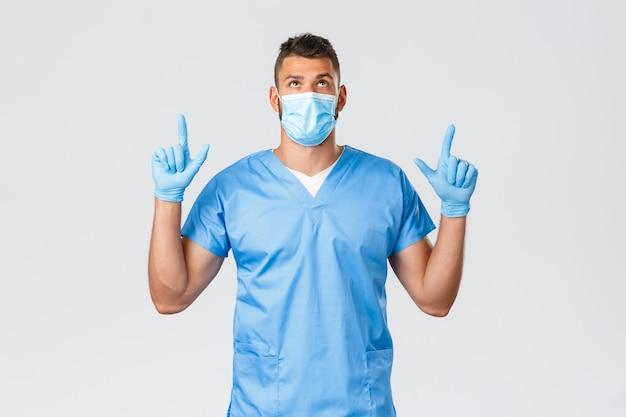 医療従事者、covid-19、コロナウイルスおよび予防ウイルスの概念。ハンサムな真面目な男性医師、スクラブと医療マスクの看護師、指を上に向けて見て、バナープロモーションを読んで