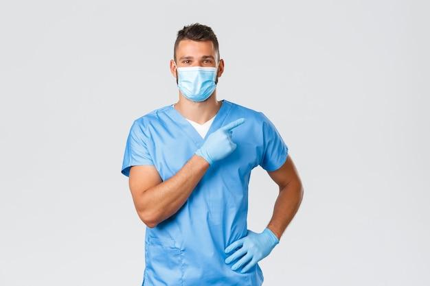 医療従事者、covid-19、コロナウイルスおよび予防ウイルスの概念。ハンサムな笑顔の医者、医療マスクとスクラブの男性看護師、右手の人差し指、クリニックのバナー、プロモーションを表示します。