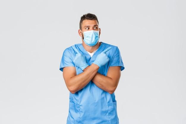 의료 종사자, covid-19, 코로나바이러스 및 예방 바이러스 개념. 흥미롭고 우유부단한 잘 생긴 의사, 수술복을 입은 남자 간호사, 의료 마스크를 선택하고 현수막을 옆으로 가리키며