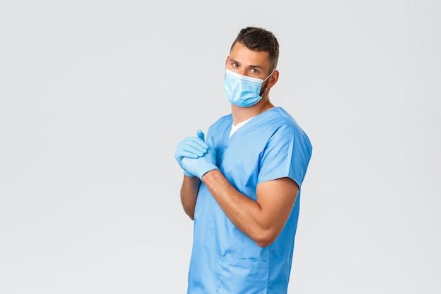 Operatori sanitari, covid-19, coronavirus e prevenzione del concetto di virus. bel dottore, infermiere in maschera medica e scrub, nocche spezzate, turno di notte in clinica, sfondo grigio