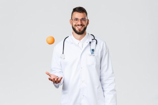 의료 종사자, 의료 보험, 클리닉 실험실 및 covid-19 개념. 쾌활하게 웃고 있는 히스패닉 의사, 흰색 코트를 입은 의사, 오렌지 던지기, 건강한 비타민 과일 섭취 권장