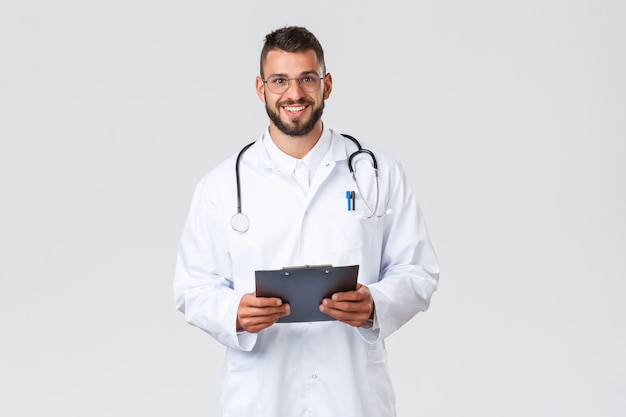 의료 종사자, 의료 보험, 클리닉 실험실 및 covid-19 개념. 청진기와 클립보드가 있는 흰색 코트를 입은 잘생긴 젊은 히스패닉 의사, 환자에게 웃고 친근한 카메라
