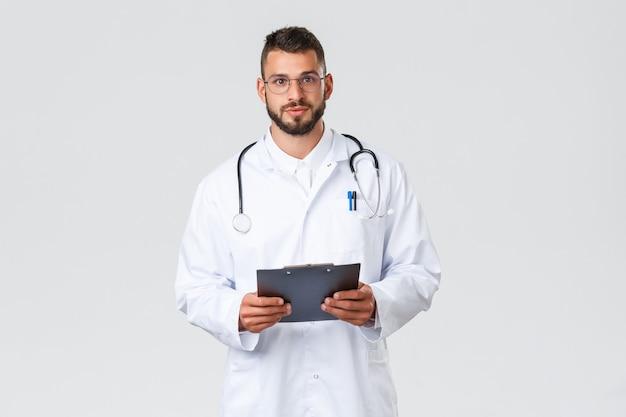 의료 종사자, 의료 보험, 클리닉 실험실 및 covid-19 개념. 청진기와 클립보드가 있는 흰색 코트를 입은 젊은 전문 히스패닉 의사, 병원에서 환자의 말