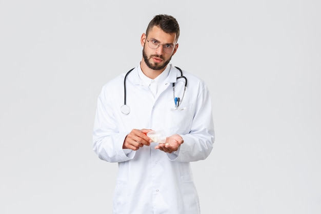 Healthcare workers, medical insurance, pandemic and covid-19 concept. serious young hispanic doctor prescribe medication, holding medicine, tell patients importance taking pills.