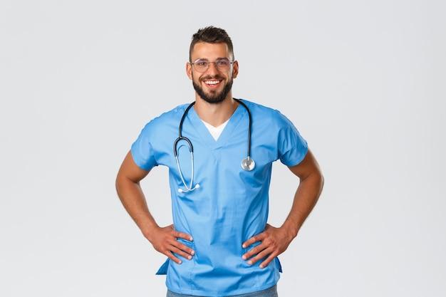 의료 종사자, 의학, covid-19 및 전염병 자가 격리 개념. 열정적인 잘생긴 의사, 안경을 쓴 남자 간호사, 파란색 수술복을 입은 남자 간호사, 병원 환자들과 즐겁게 일하면서 웃고