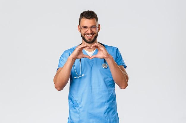 Медицинские работники, медицина, covid-19 и концепция самокарантина при пандемии. улыбающийся красивый доктор в очках и скрабах, врач выражает любовь и заботу, показывая пациентам знак сердца
