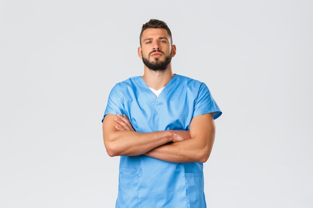 Operatori sanitari, medicina, covid-19, concetto di auto-quarantena pandemica. fiducioso medico ispanico forte, dall'aspetto serio, infermiere in camice blu, mani incrociate sul petto sicuro di sé, salva i pazienti.