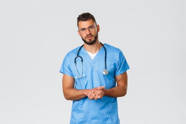 Operatori sanitari, medicina, covid-19 e concetto di auto-quarantena pandemica. medico professionista, chirurgo o medico in clinica che parla con un paziente con una faccia gravemente preoccupata, indossa uno scrub blu