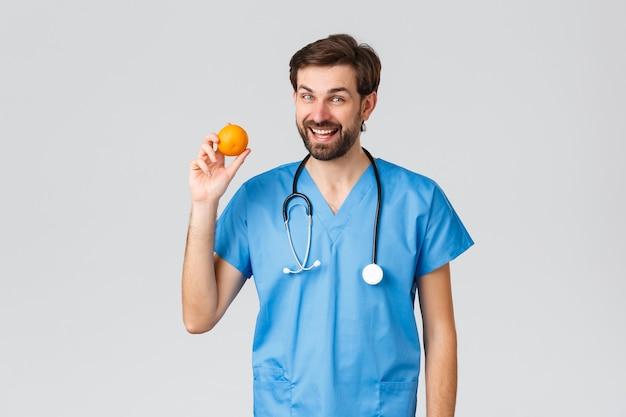 医療従事者、パンデミックおよびコロナウイルスの発生の概念。医者はもっとビタミンを食べることを提案します。スクラブで陽気な医師や看護師は、オレンジを保持し、笑顔で健康的な食べ物を食べるように言います