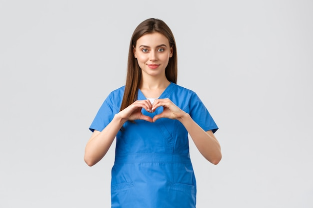 Медицинские работники, предотвращение вирусов, страхование и концепция медицины. улыбающаяся привлекательная женщина-врач, медсестра в синих халатах, оставайтесь дома, демонстрируйте знак сердца, выражайте уважение борцам с коронавирусом.
