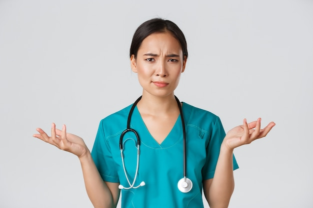 Healthcare workers, preventing virus, quarantine campaign concept. close-up of confused and puzzled asian female physician in scrubs having complicated problem, raising hands and shrugging