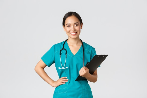 Healthcare workers, preventing virus, quarantine campaign concept. smiling pleasant asian female physician, doctor during examination wearing scrubs and holding clipboard, white background.