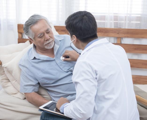 Азиатский старший пожилой старик с маской на лежать на софе пока молодой кавказский доктор сидит на проверке колена его сердцебиение и старая старшая женщина сидит рядом с заботой и беспокойством концепция .healthcare.
