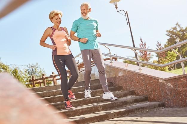 행복해 보이는 운동복을 입은 활동적인 성숙한 가족 커플의 건강하고 행복한 전체 길이 사진
