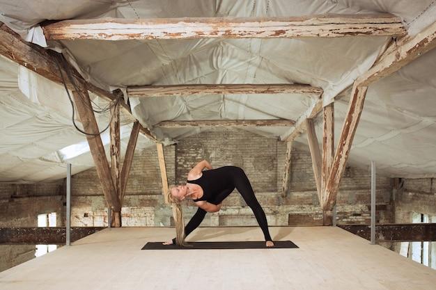 건강한. 젊은 체육 여자 버려진 된 건설 건물에 요가 연습. 정신적 및 신체적 건강 균형. 건강한 라이프 스타일, 스포츠, 활동, 체중 감소, 집중력의 개념.