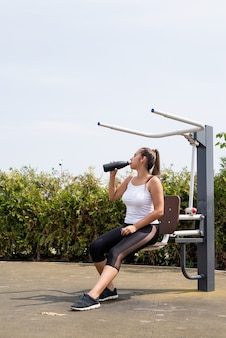 Healthy and active lifestyle. sports and fitness. happy woman in white t shirt working out on the sports ground in sunny summer day, drinking water from the thermos bottle