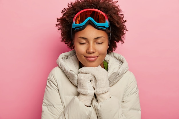 Healthy adorable woman with curly hair, wears white down padded coat and mittens, uses ski mask, eyes shut