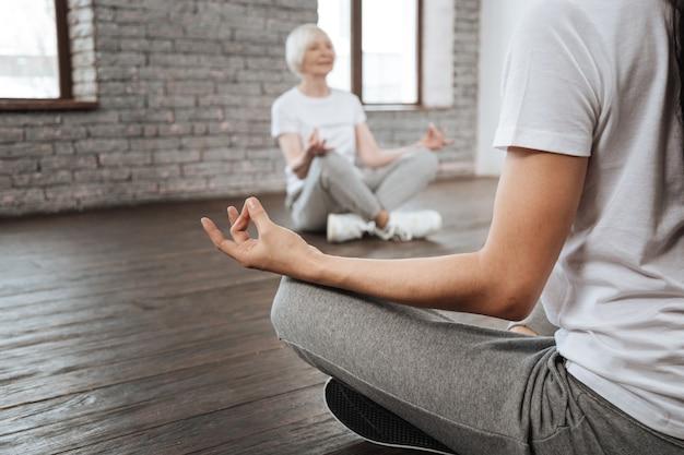 Здоровая пожилая женщина сидит в позе йоги, держа спину прямо во время выполнения упражнений для медитации