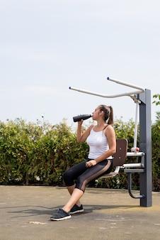 건강하고 활동적인 라이프 스타일. 스포츠 및 피트니스. 화창한 여름날 운동장에서 운동하는 흰색 티셔츠를 입은 행복한 여성, 보온병에서 물을 마시는