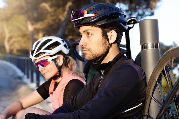 健康的でアクティブなライフスタイル。長いライドの後、朝に橋で休んでいる2人の自転車旅行者、ポジティブな思慮深い顔の表情を持つハンサムでカリスマ的な若いひげを生やした男に選択的に焦点を当てる