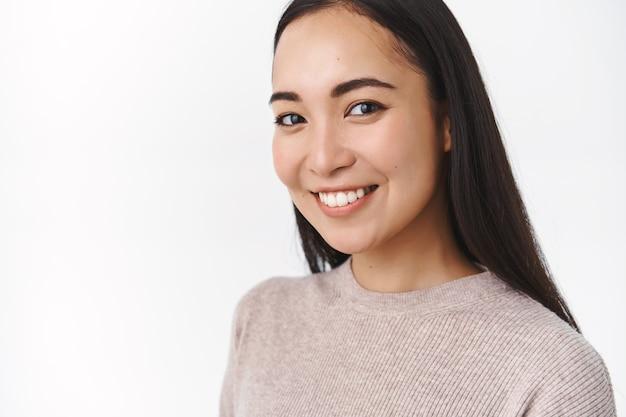 건강하고 활동적인 웃고 있는 쾌활한 아시아 여성, 고개를 기울인 채 행복하고 카메라를 응시하며 웃고, 새로운 스킨케어 일상을 시작했습니다.