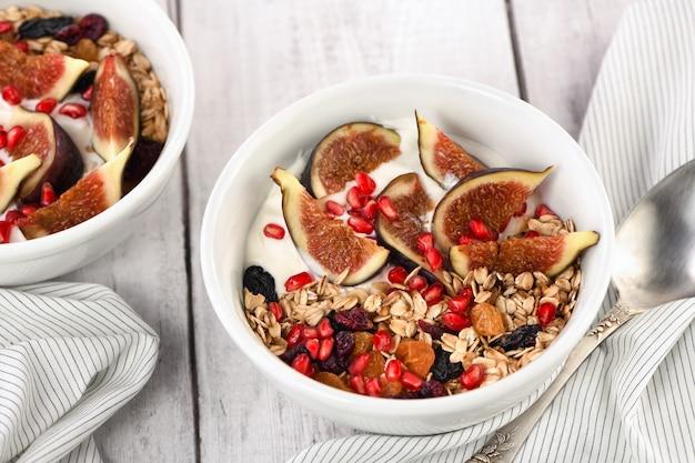 건강하고 맛있는 아침 식사. 그리스 요구르트, 신선한 무화과, 말린 과일, 석류를 곁들인 오트밀 뮤즐리.