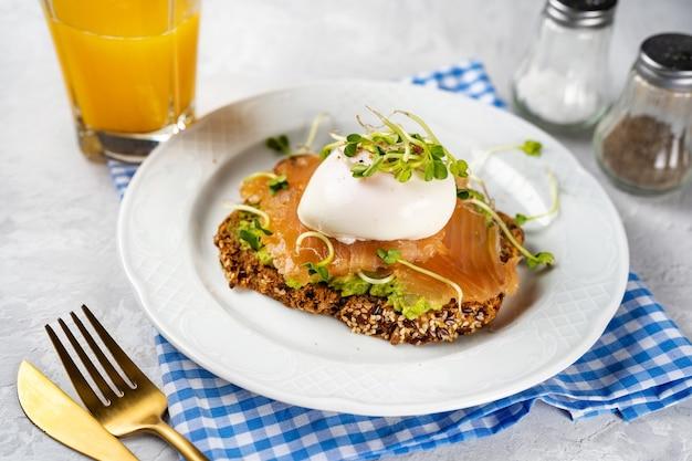 아침이나 가지로 아보카도, 연어, 수란, 마이크로 그린을 곁들인 건강하고 맛있는 토스트입니다. 가정에서 편안한 요리. 페스 카트 리안 다이어트. 두뇌 음식. 오메가 3 지방.