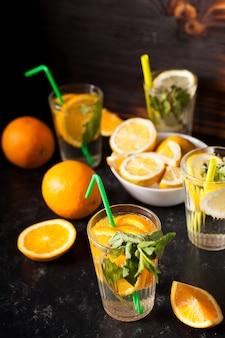 짙은 빈티지 나무 배경에 자른 과일 옆에 레몬과 오렌지로 만든 건강하고 맛있는 디톡스 물