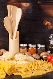 健康的でおいしい食事-素朴なヴィンテージの木製の背景に野菜の横にある生の生パスタ