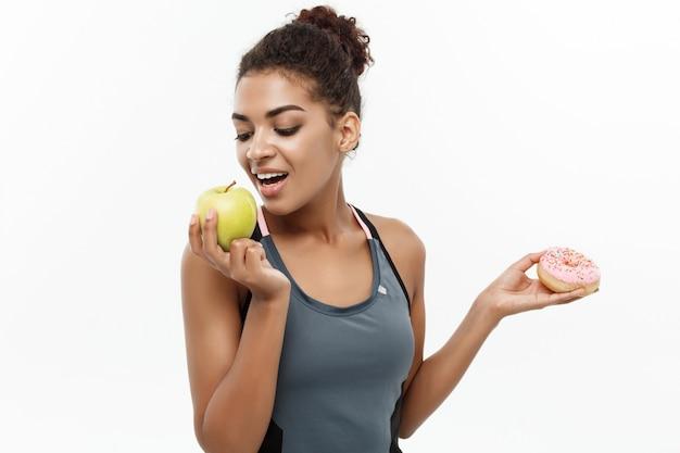 건강 및 다이어트 개념-아름 다운 스포티 한 아프리카 계 미국인 도넛과 녹색 사과 사이 결정을 내립니다. 흰 배경에 고립.