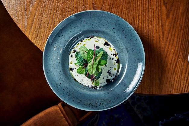 ヘルシーでダイエット食品-クリーミーなソースで煮込んだ芽キャベツとほうれん草を木製のテーブルの青いプレートに添えて。上から見る