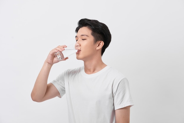 Здоровый и счастливый молодой человек пьет воду во время отдыха дома