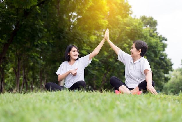 건강하고 라이프스타일 개념, 아시아 여성은 아침에 손을 들고 공공 공원에서 함께 휴식을 취하고, 행복과 미소, 긍정적인 생각