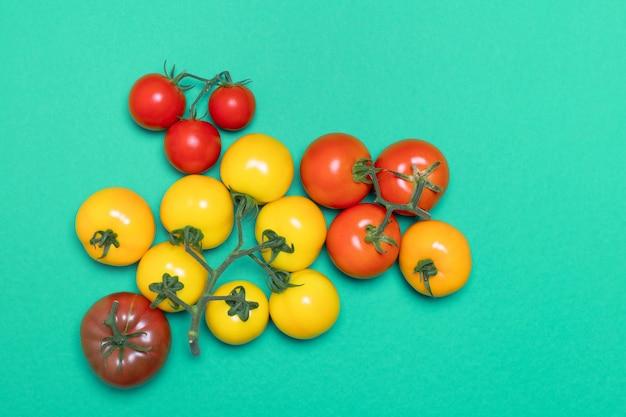 緑の背景に分離されたさまざまな色の健康的で有機的なトマト